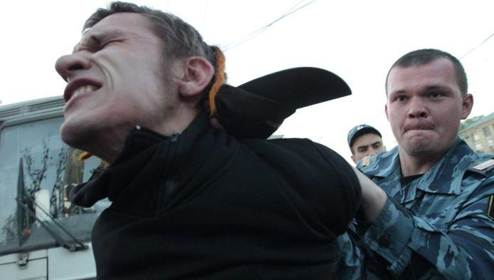 Een Russische agent arresteert een deelnemer aan Occupy Moskou, vorige week.