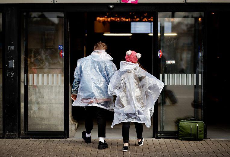 2018-01-18 12:00:08 AMSTERDAM - Mensen trotseren de storm op straat voor Amsterdam Centraal Station. ANP ROBIN VAN LONKHUIJSEN Beeld ANP