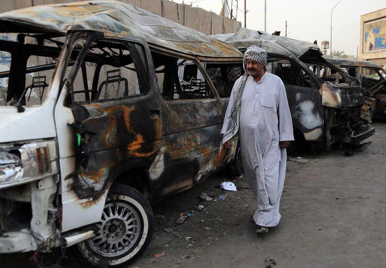 Een man bezoekt in Bagdad de plek waar gisteren een autobom ontplofte. Beeld ap