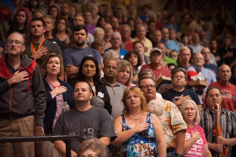 Aanhangers van Trump tijdens het volkslied op een bijeenkomst in Canton, Ohio. Trump bezocht zoveel mogelijk cruciale staten sinds Clinton ziek thuis zit. Beeld AFP