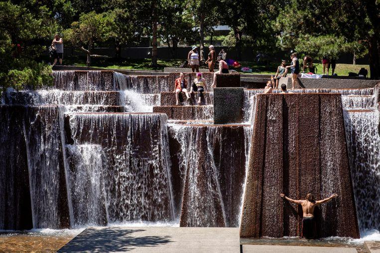 Mensen zoeken verkoeling in een fontein in Portland, Oregon. Beeld REUTERS