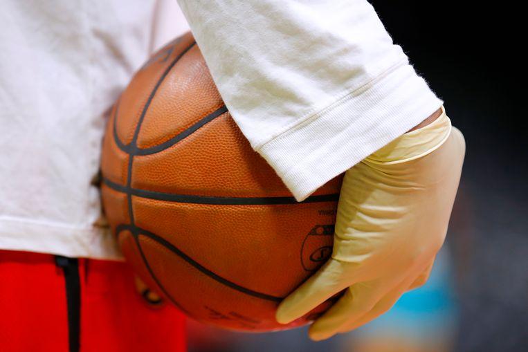 Ballenjongens dragen handschoenen bij de NBA-basketbalwedstrijd Charlotte Hornets-Atlanta Hawks in Amerika. Beeld Getty Images