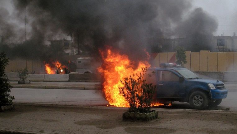 Een brandende politieauto in de Iraakse stad Falluja Beeld epa