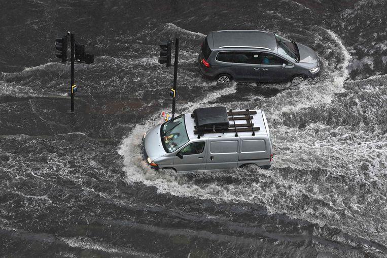 Auto's banen zich een weg door het water in Nine Elms, Londen, zondag 25 juli. Beeld AFP