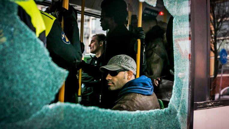 Een vernielde bus met daarin tegenstanders van Zwarte Piet bij het politiebureau van Maassluis. Beeld anp