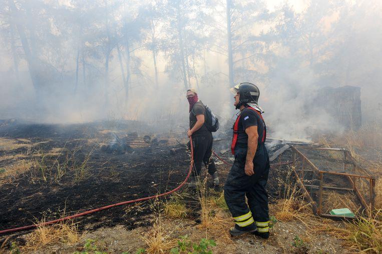 Een brandweerman en een vrijwilliger blussen een brand op het Griekse eiland Rhodos. Beeld EPA