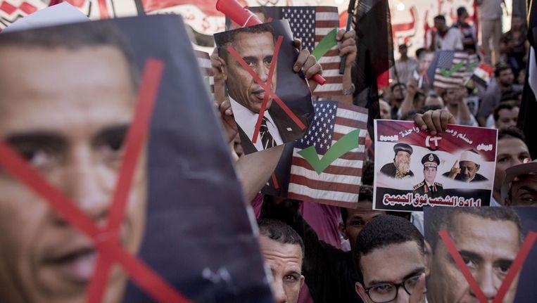 Demonstranten in Egypte houden posters met een doorgestreept gezicht van de Amerikaanse president Obama omhoog. Beeld getty