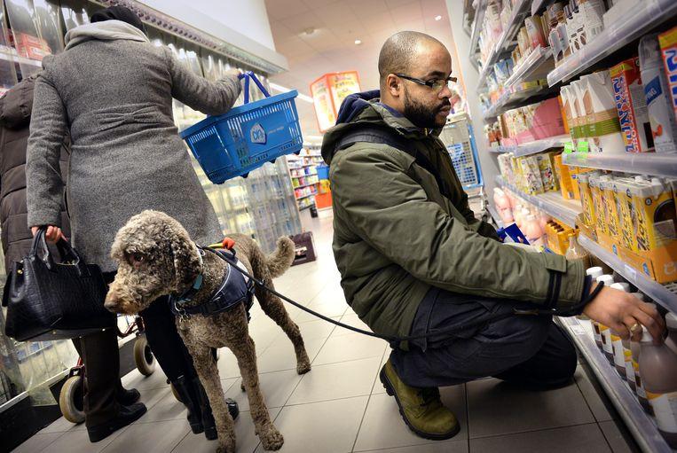 Trevor met PTSS en zijn hulphond in de supermarkt. De hond zorgt dat passanten afstand houden. Beeld Marcel van den Bergh