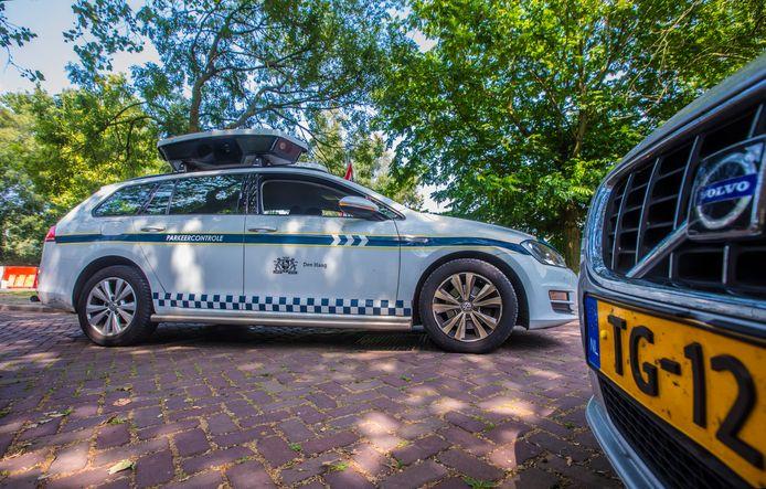 Een scanauto aan het werk in Den Haag. Op het dak zitten camera's die kentekens van geparkeerde voertuigen lezen.