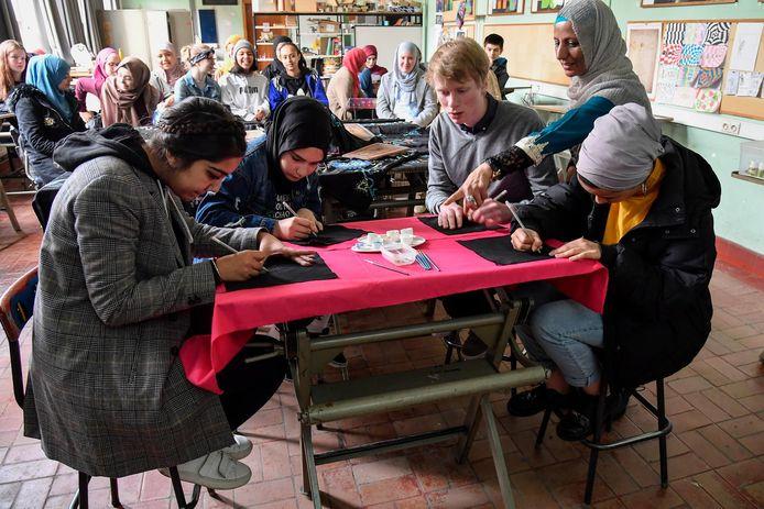 Onder kundige begeleiding leren de leerlingen omgaan met kalligrafie.