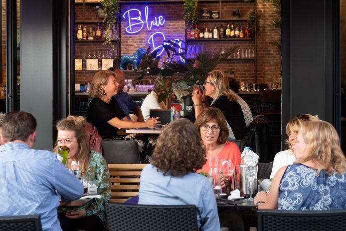 Eten op terras bij Blue Dog, met een doorkijk naar binnen.