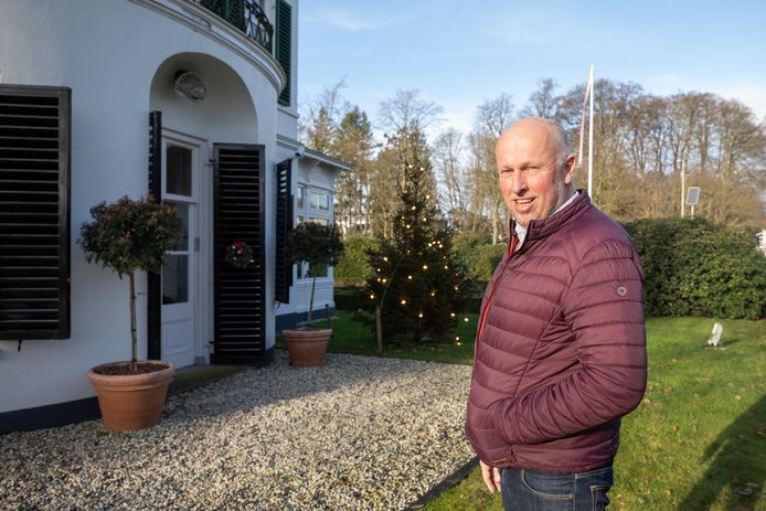 Hans Hoekzema voor zijn villa Buitenzorg. Tussen het pand en de kerstboom is de Soester vleugel van Paleis Soestdijk te zien.