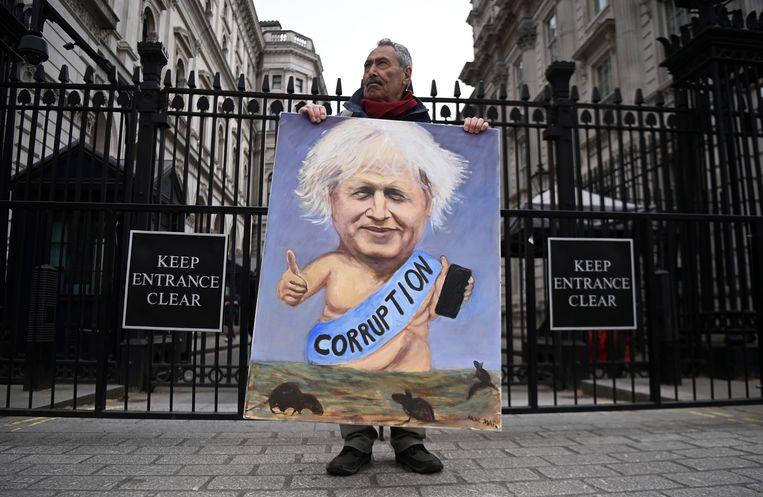 Kunstenaar Kaya Mar protesteert met een eigen spotprent tegen de Britse premier Boris Johnson buiten diens woning aan Downing Street. Beeld EPA