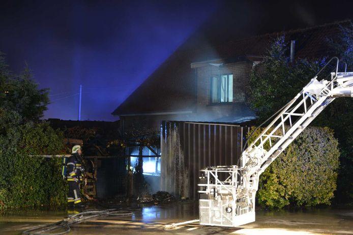 Een brandweerman voor het getroffen huis, waar een ploeg met lampen op zoek is naar resterende brandhaarden.