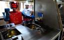 Een kok in de Chinese stad Hefei kijkt toe hoe een robot voedsel bereidt.