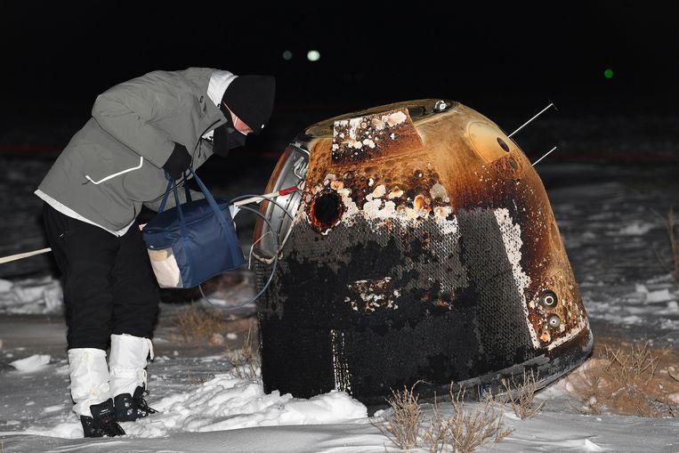 Een Chinese onderzoeker buigt zich over de maansonde Chang'e 5. Die landde gisteren in de noordelijke provincie Binnen-Mongolië na een terugreis vanaf de maan van twee weken. De sonde bracht twee kilo maanstenen en ander bodemmateriaal mee naar huis.  Beeld REUTERS