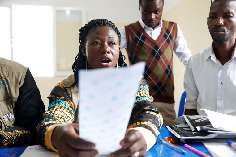 Een medewerker van de Congolese kiescommissie leest de resultaten voor van een stembureau in Kinshasa.  Beeld REUTERS