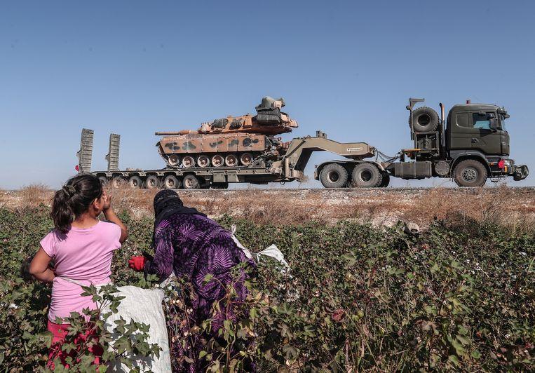 Koerdische seizoenarbeiders zien hoe het Turkse leger met tanks Noord-Syrië binnenrijdt. Beeld EPA