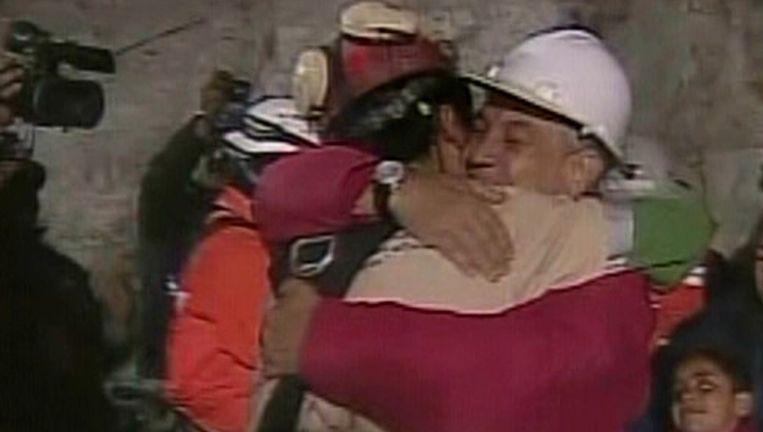 Florencio Avalos, de eerste geredde mijnwerker, valt opgelucht zijn dierbaren in de armen. Beeld UNKNOWN