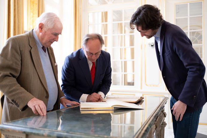 HINGENE Het gulden boek komt terug naar het kasteel d'Ursel. Emmanuel d'Ursel en Emmanuel d'Hennezel tonen het oude en het nieuwe boek, directeur Koen De Vlieger kijkt toe.