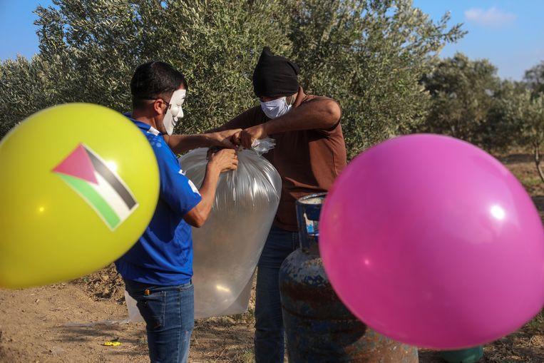 Palestijnen maken brandgevaarlijke ballonnen klaar die ze aan de grens met Israël oplaten. Beeld EPA