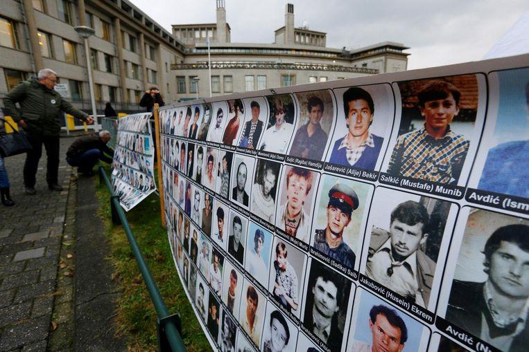 Demonstranten hangen foto's op buiten het Joegoslaviëtribunaal in Den Haag Beeld reuters