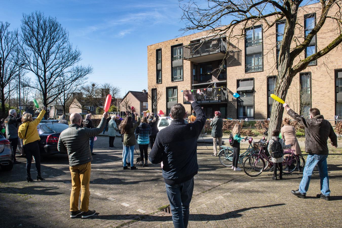 Familieleden en buurtbewoners brengen een aubade aan de honderd jaar geworden Hermina Mali-Gijsberts bij verpleeghuis De Vlechting in de Nijmeegse wijk Zwanenveld.