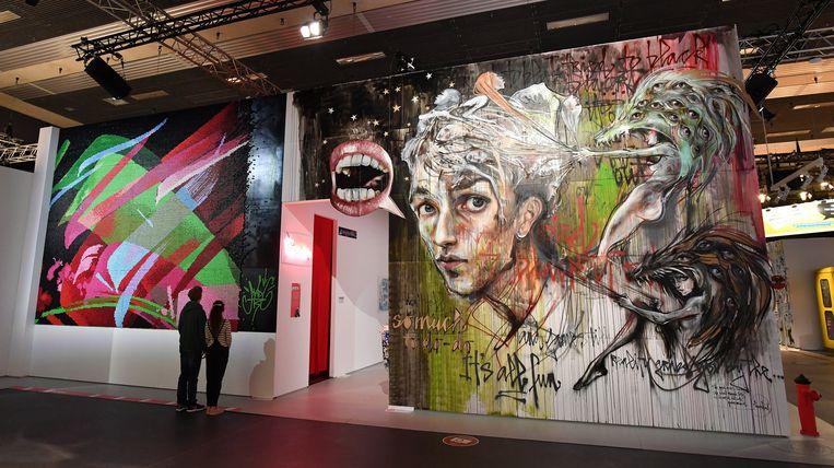 Werk van MadC (links) naast werk van het duo Herakut op een expo deze maand in München.  Beeld EPA