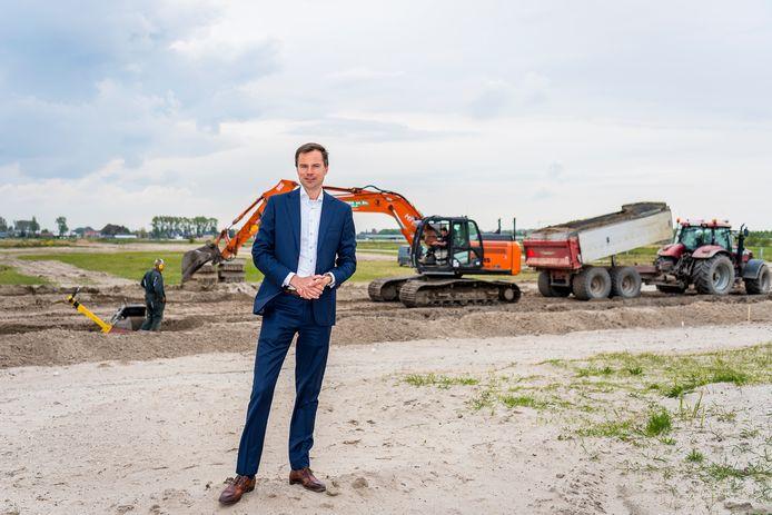 Wethouder Jan-Willem van den Beukel op het terrein waar de nieuwbouwwijk Wilderszijde moet verrijzen. De aannemer achter hem is bezig met de aanleg van een weg voor het bouwverkeer.