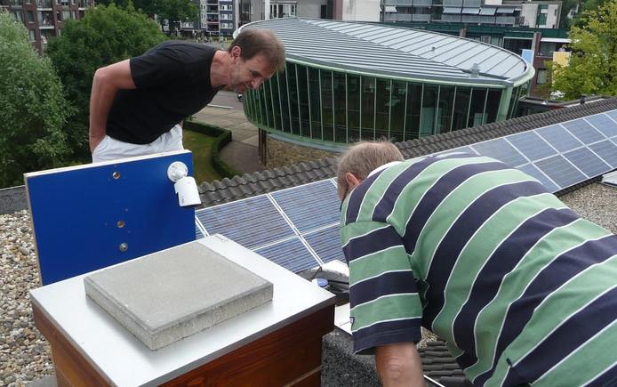 Wethouder Peter van de Wiel en imker Han Goossens bekijken de bijenkast op het dak van het Boxtelse gemeentehuis. Op de achtergrond de karakteristieke raadzaal.