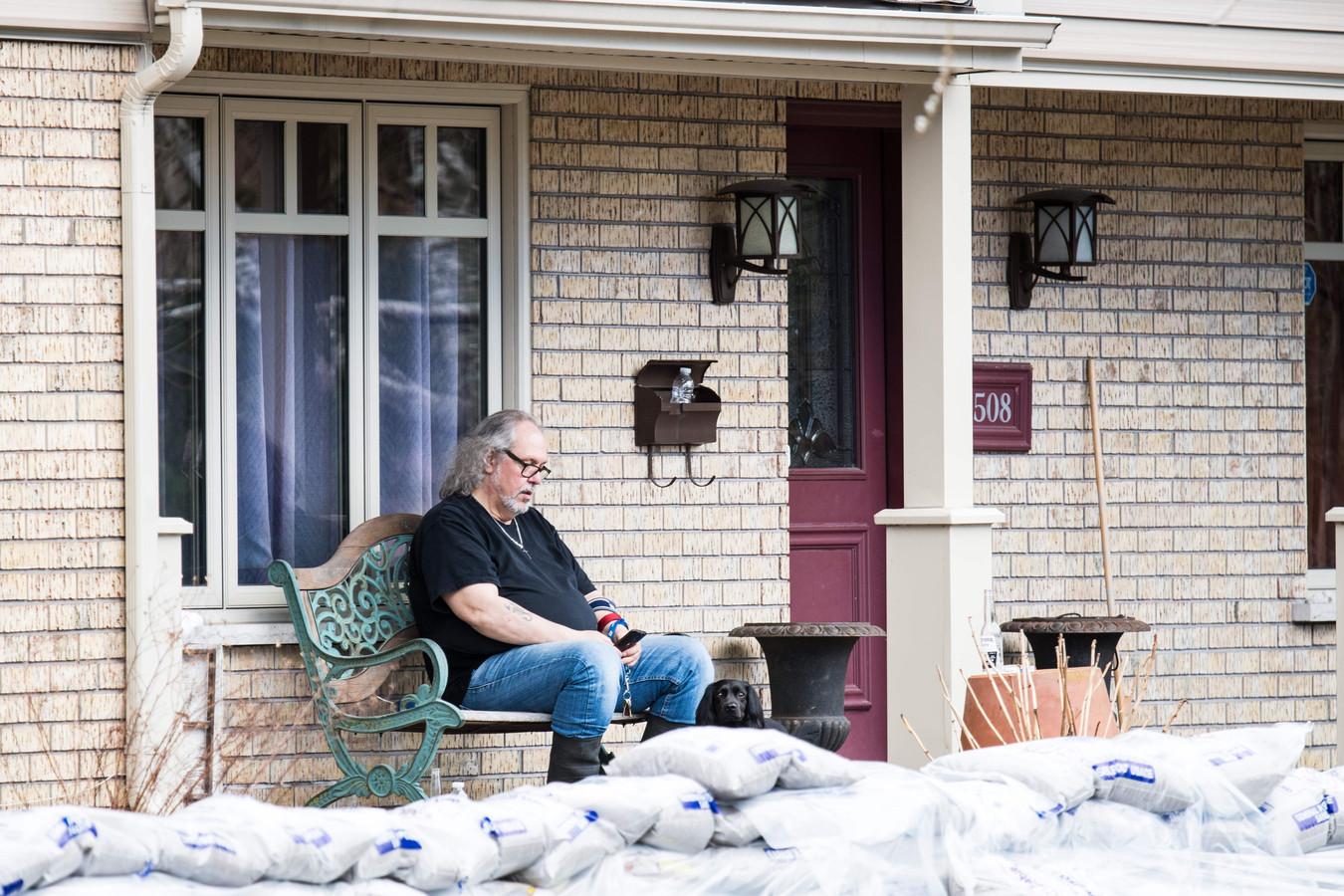 Een man heeft zijn huis gebarricadeerd met zandzakken.