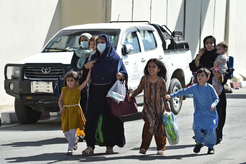Een Afghaanse familie op de luchthaven van Kaboel. Beeld AFP