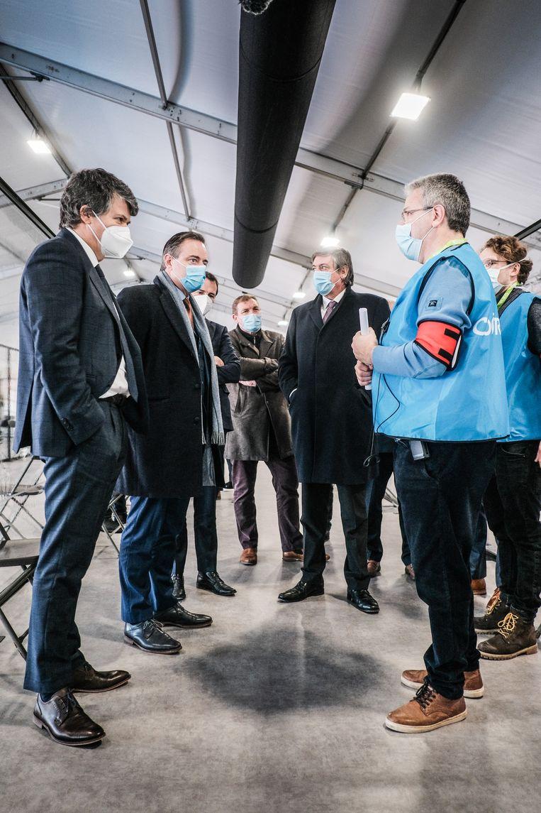 Vlaams minister van Binnenlands Bestuur Bart Somers (Open Vld), burgemeester Bart De Wever (N-VA) en diens partijgenoot, minister-president Jan Jambon worden rondgeleid in het Antwerpse vaccinatiecentrum op Spoor Oost.  Beeld Bob Van Mol