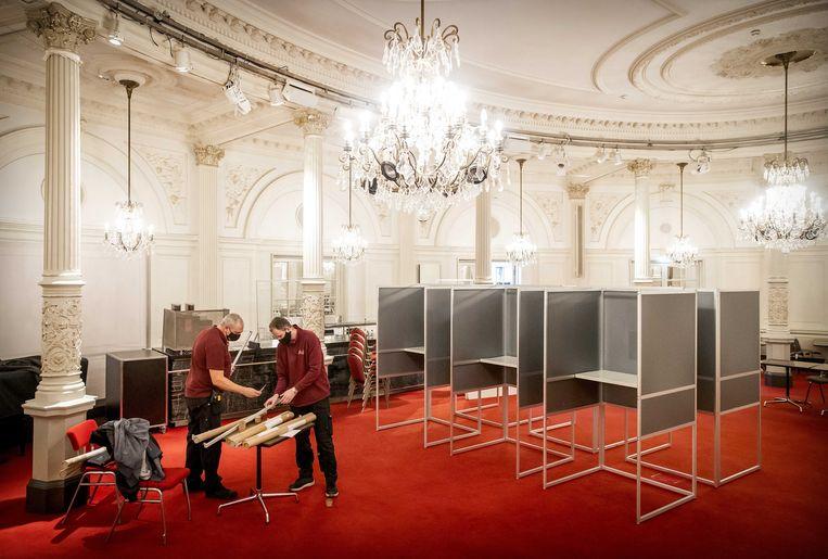 Vrijwilligers tijdens de opbouw van een stembureau in de Spiegelzaal van het Amsterdamse Concertgebouw.  Beeld ANP