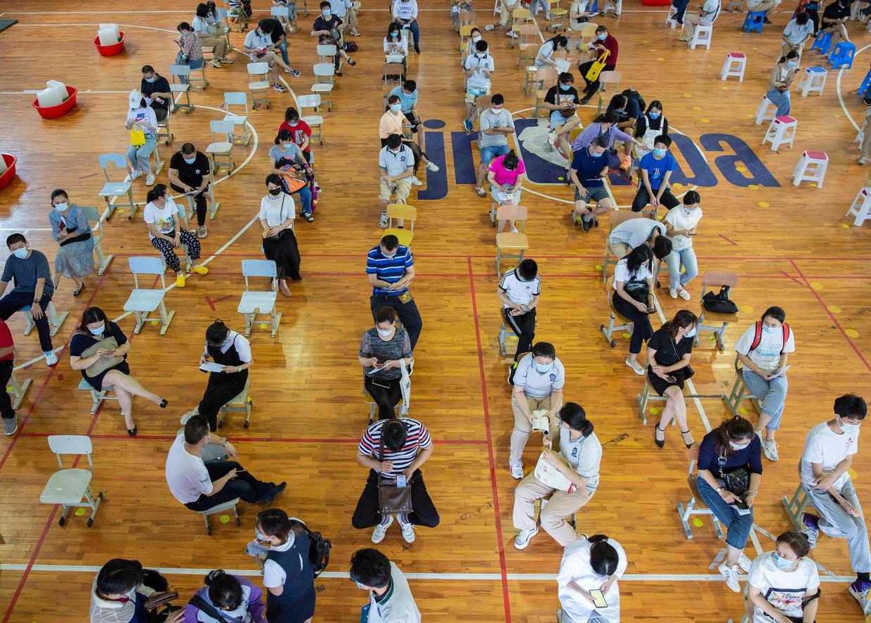 Chinese studenten wachten op hun vaccin in de Chinese stad Nanjing. Beeld AFP
