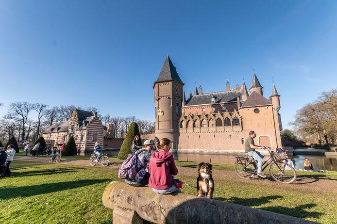 Wandelaars genieten van de zon bij kasteel Heeswijk waar een week geleden nog werd geschaatst.