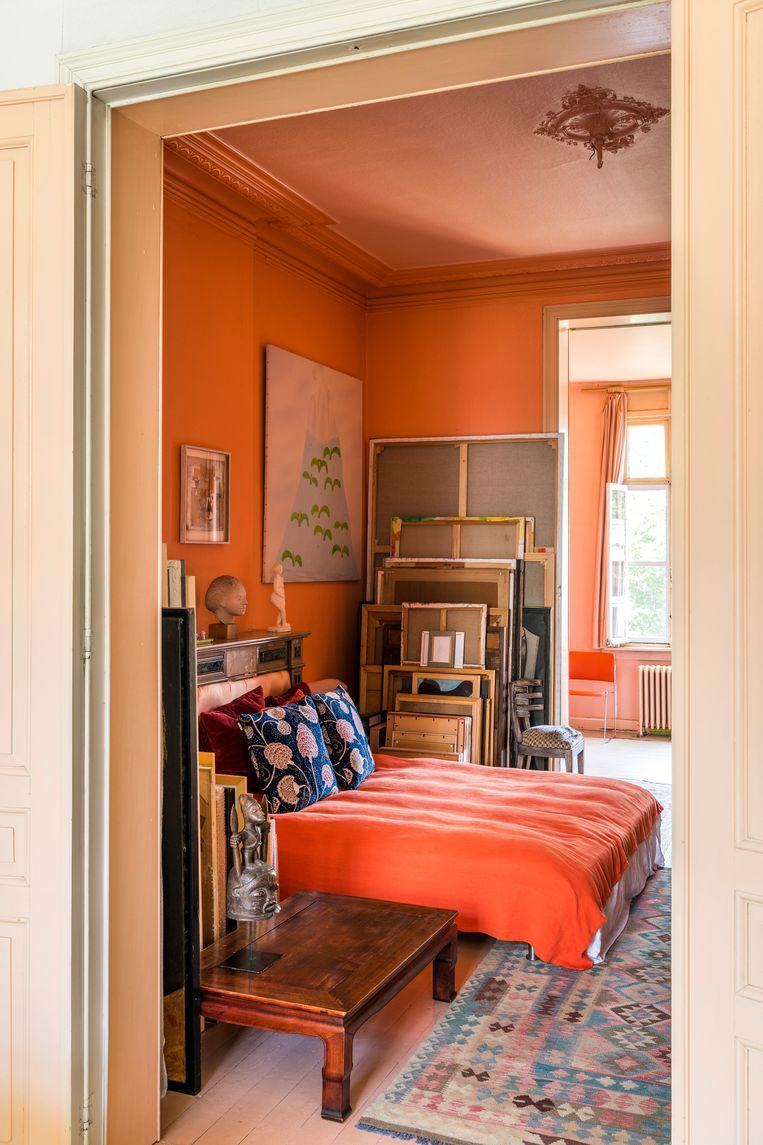 De opgestapelde werken van Herman Maes komen tot tegen het bed. De feloranje muren herinneren aan de vorige bewoonster, popartkunstenares Hélène Keil. Ook het pastelkleurige schilderij aan de muur is van haar hand. De twee beeldjes op de schouw zijn van Carly Vanoverbeke.  Beeld Luc Roymans