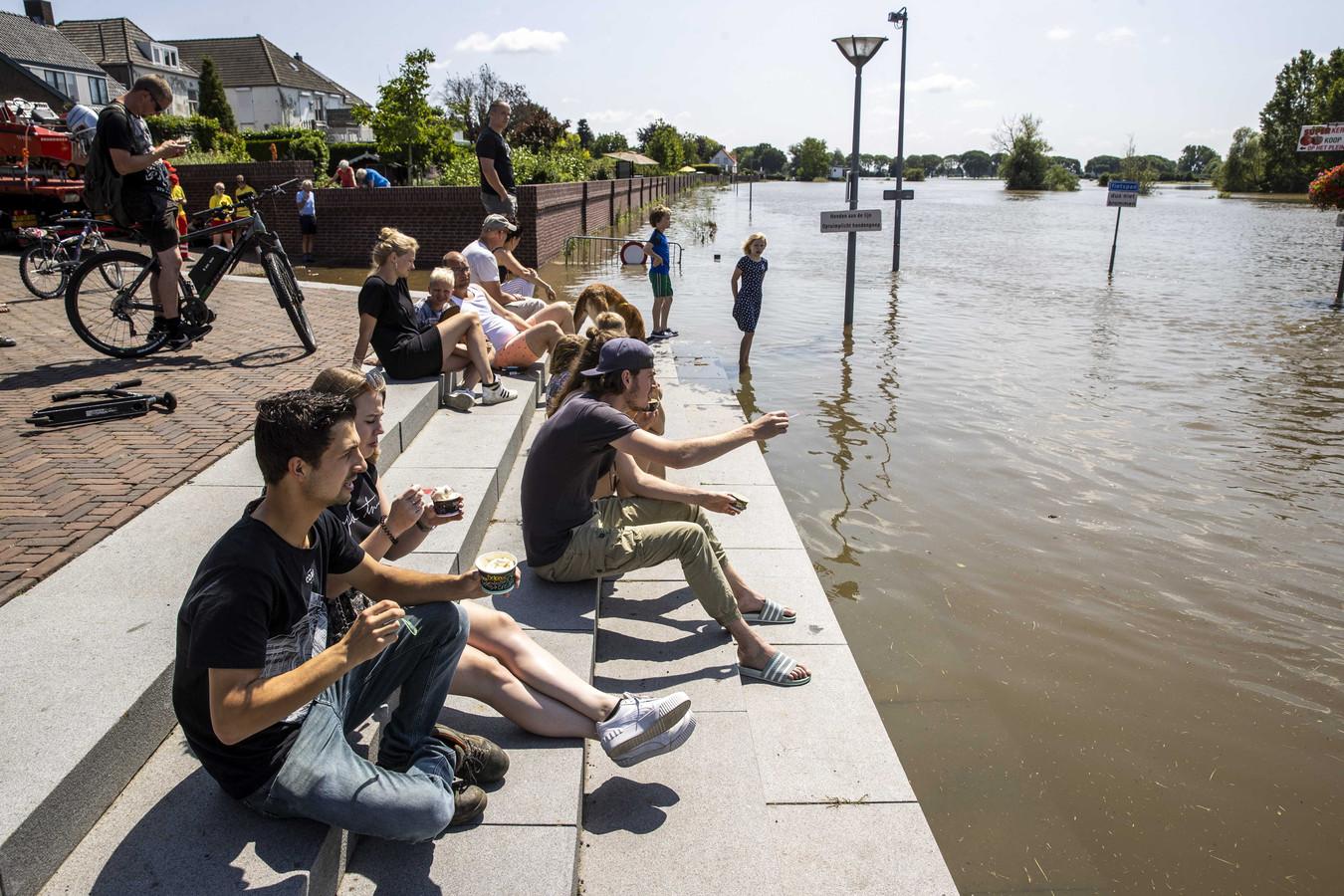 Toeschouwers kijken naar het hoge water van de Maas in het centrum van Mook.