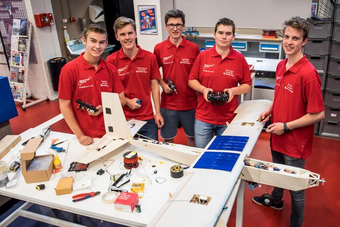 Vijf van de zes studenten die verantwoordelijk zijn voor het maken van het zonnevliegtuig dat voor hen ligt.