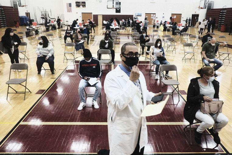 Gevaccineerden nemen plaats op een van de vijftig klapstoeltjes in het midden van de zaal om eventuele duizeligheid te ondervangen.  Beeld AFP