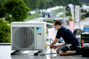 Een monteur installeert een airco bij een bedrijf. Foto ter illustratie.