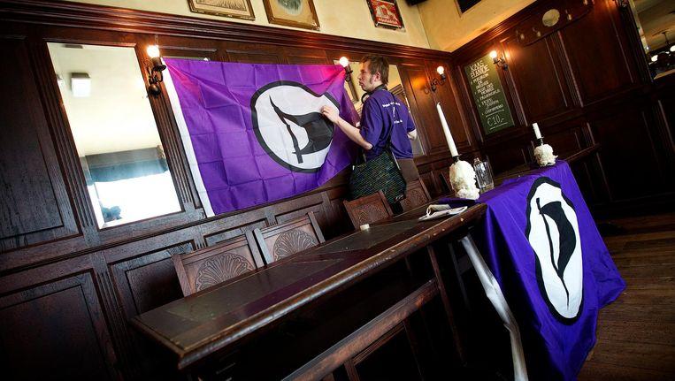 Een lid van de Piratenpartij hangt de partijvlag op. Beeld anp