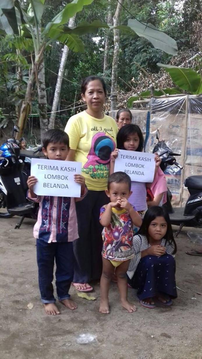 'Bedankt Lombok Nederland' staat er op deze papieren die de kinderen op het eiland omhoog houden.