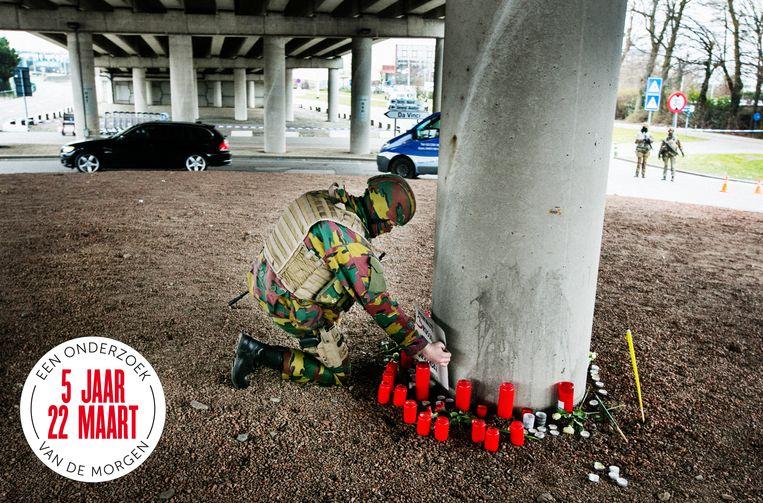 Een militair zet een omgevallen bordje terug op zijn plaats op een herdenkingsplek voor de slachtoffers in Zaventem. Beeld Tim Dirven