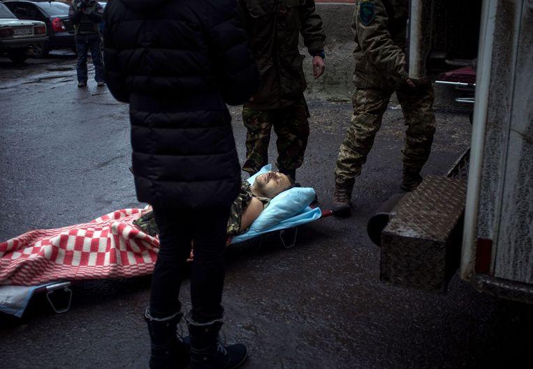 Een gewonde Oekraïense soldaat wordt naar een ziekenhuis gebracht. Beeld AFP