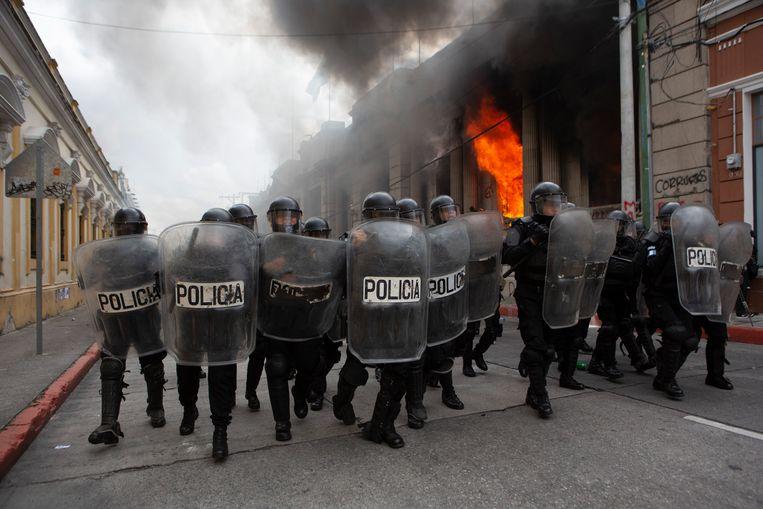 Oproerpolitie vormt een cordon om te voorkomen dat demonstranten het parlementsgebouw bestormen. Beeld AP