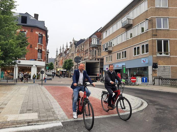 Schepen David Dessers en schepen Dirk Vansina rijden het nieuwe fietspad in.