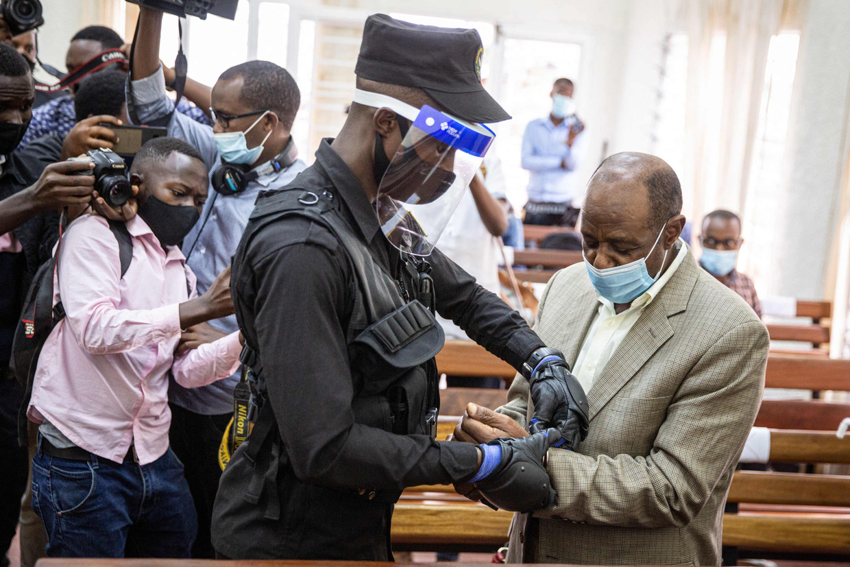 Een Rwandese agent boeit Rusesabagina in de rechtbank in Kigali.  Beeld AFP