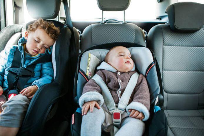 Kinderen in slaap op de achterbank van een auto.