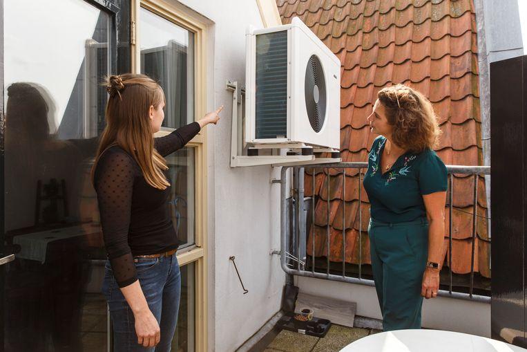 Bewoner en duurzaam ondernemer Jill Vervoort (l) laat de warmtepomp op haar balkon zien aan de Amsterdamse wethouder Van Doorninck (klimaat). Beeld De gezonde stad